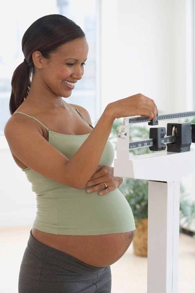 Pregnant African woman on scale : Stock Photo