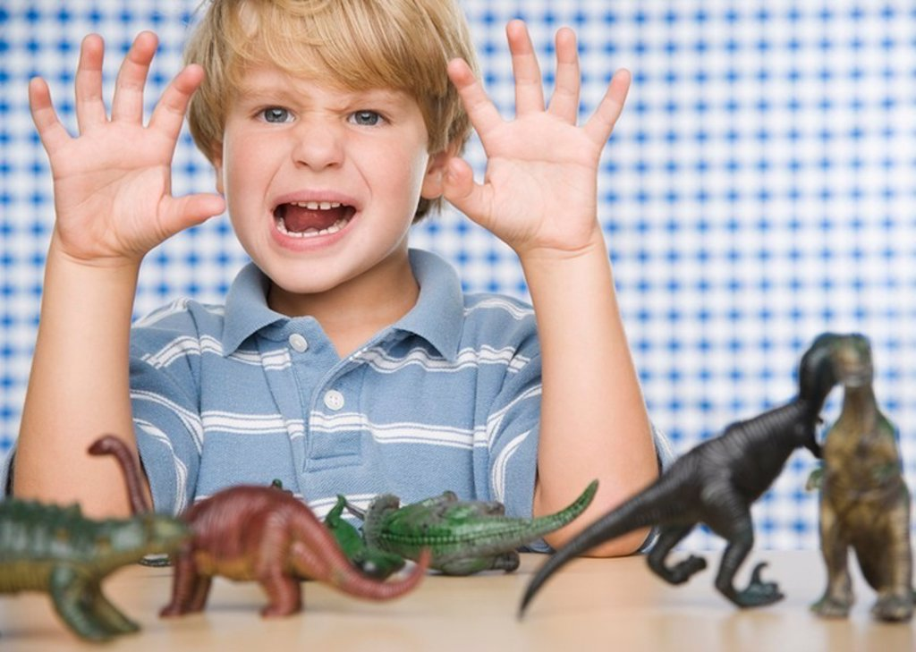 Stock Photo: 1589R-100688 Young boy making face with toy dinosaurs