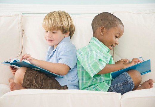 Two young boys reading on sofa : Stock Photo