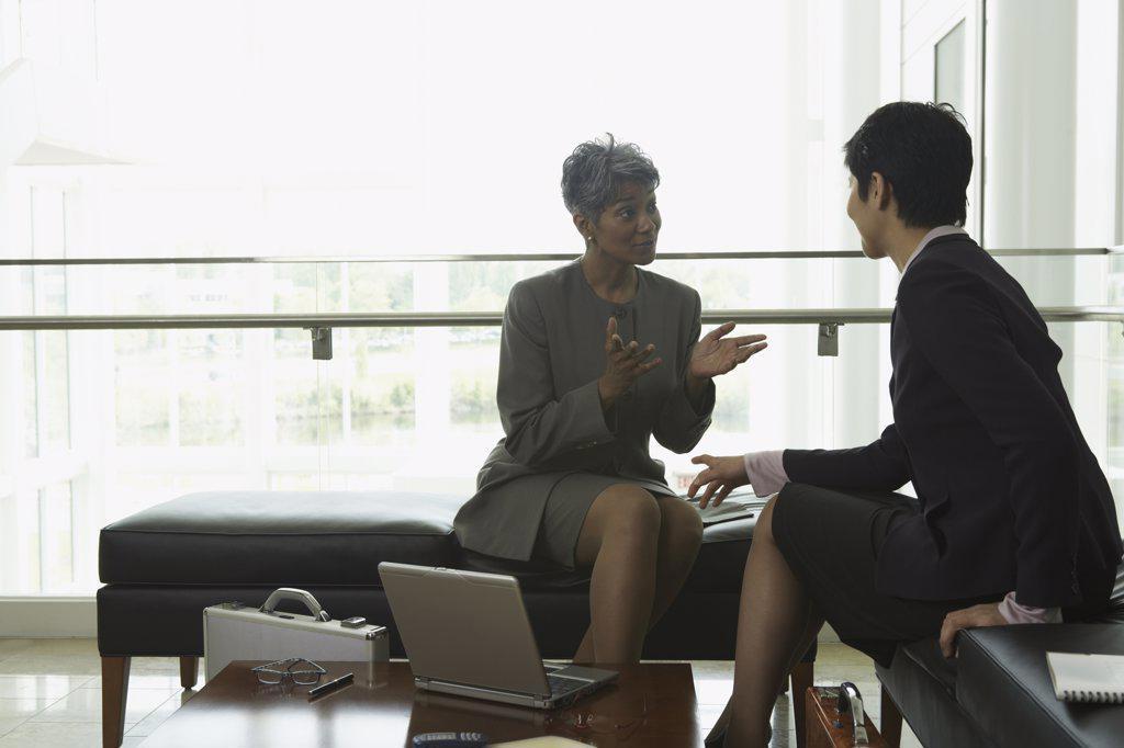 Stock Photo: 1589R-10968 Two businesswomen conferring