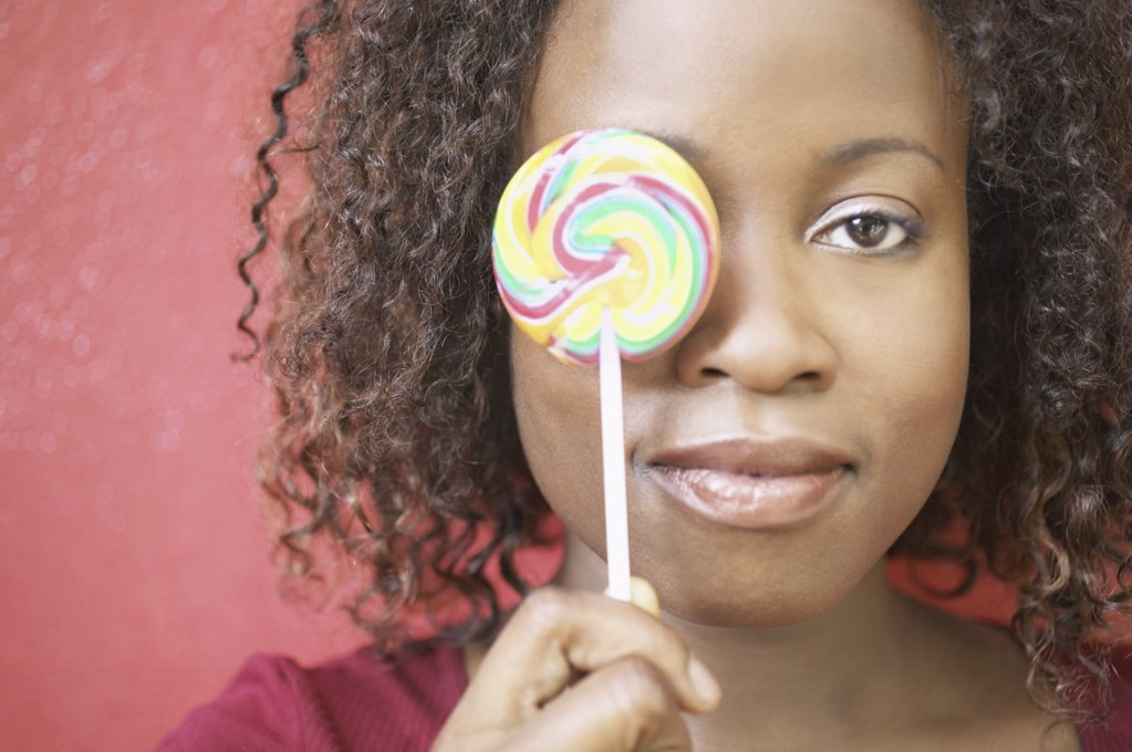 Woman holding lollipop in front of her eye : Stock Photo