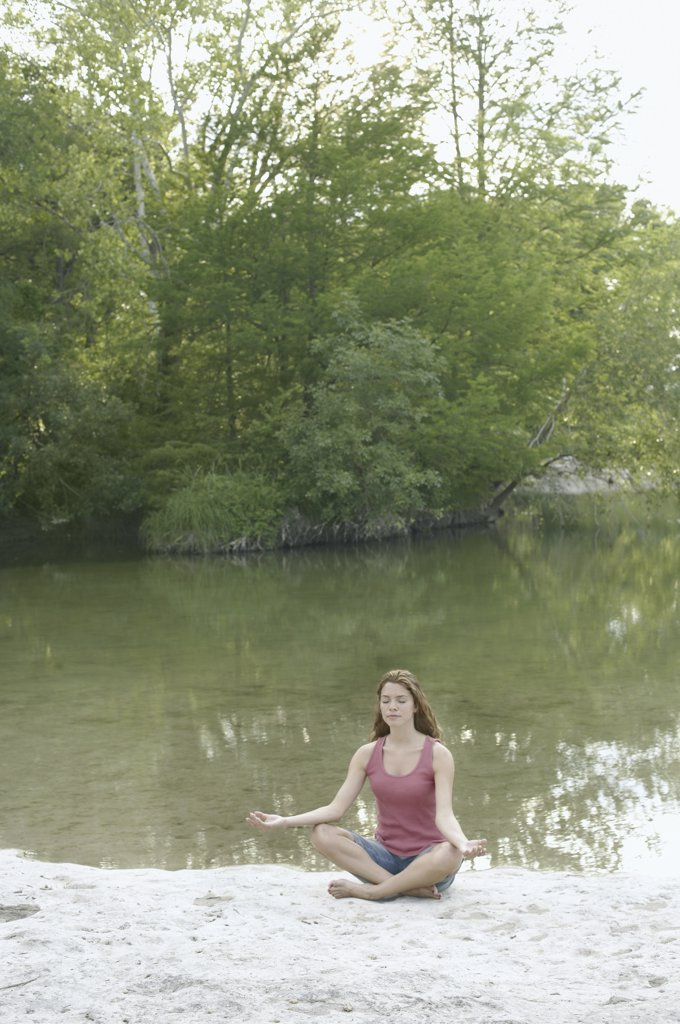 Stock Photo: 1589R-11809 Woman in lotus position beside water