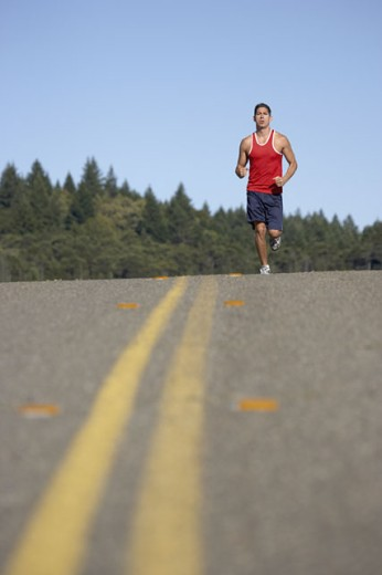 Stock Photo: 1589R-11858 Man running down a road