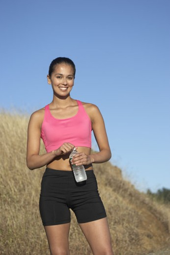 Stock Photo: 1589R-11870 Female athlete posing on grassy hill