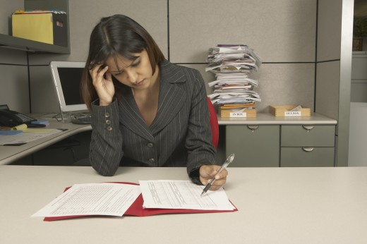Businesswoman reviewing paperwork at desk : Stock Photo
