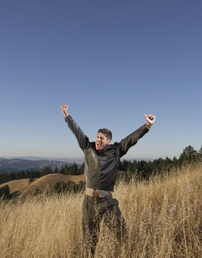 Elated man standing in field : Stock Photo