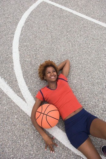 African woman laying on basketball court : Stock Photo
