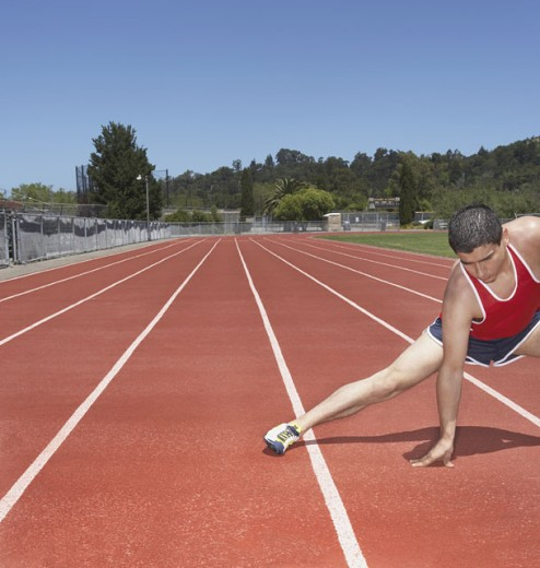 Stock Photo: 1589R-12101 Male track athlete stretching