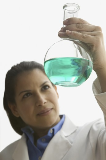 Woman in lab coat studying vial of chemicals : Stock Photo