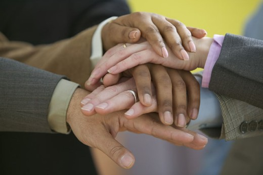 Close up of five hands stacked on top of each other : Stock Photo