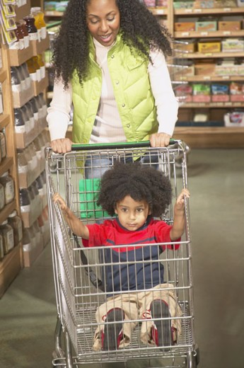 Stock Photo: 1589R-12871 Mother pushing a shopping cart while her son sitting in it