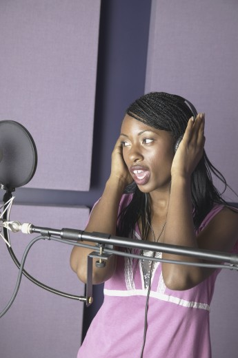 Young woman smiling in a recording studio : Stock Photo