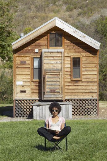 Woman reading in chair outside cabin  : Stock Photo