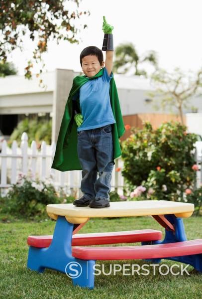 Stock Photo: 1589R-131547 Korean boy in superhero costume with arm raised