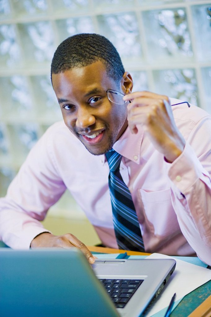 African American businessman sitting at desk : Stock Photo