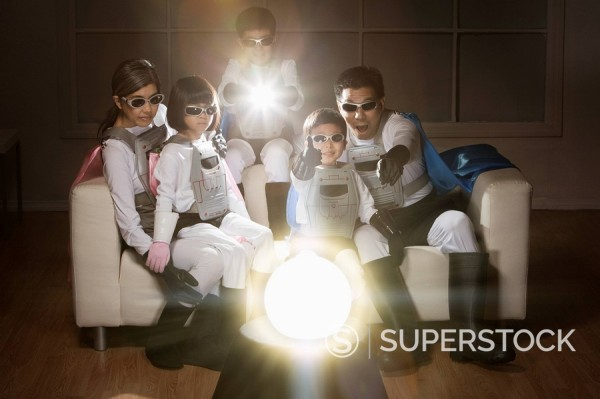 Asian superhero family watching glowing orb : Stock Photo