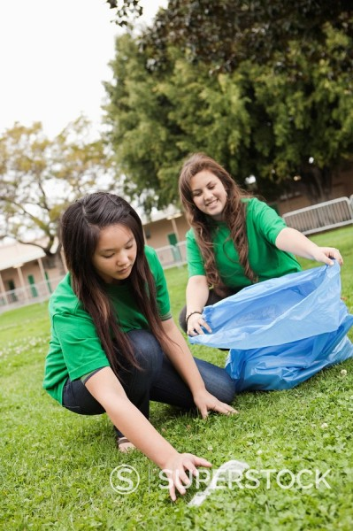 Students picking litter on school grounds : Stock Photo