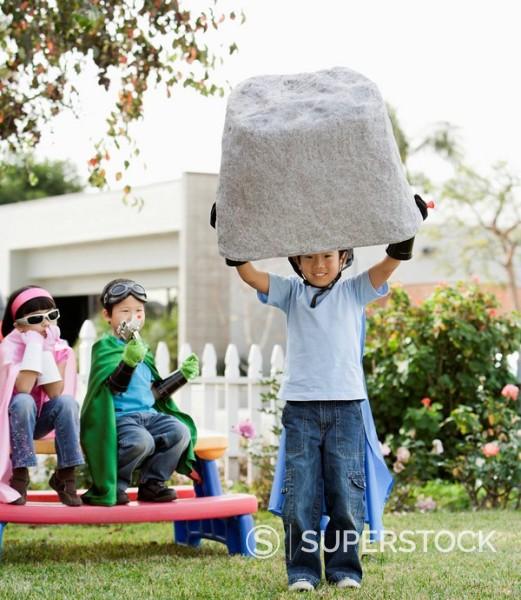 Stock Photo: 1589R-131714 Korean boy as superheros lifting large boulder