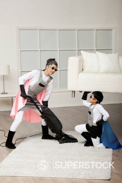 Stock Photo: 1589R-131715 Korean superhero son lifting sofa for mother to vacuum underneath