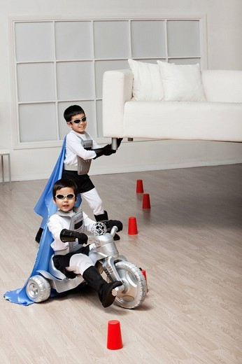 Korean superhero boy lifting sofa for brother to ride underneath : Stock Photo