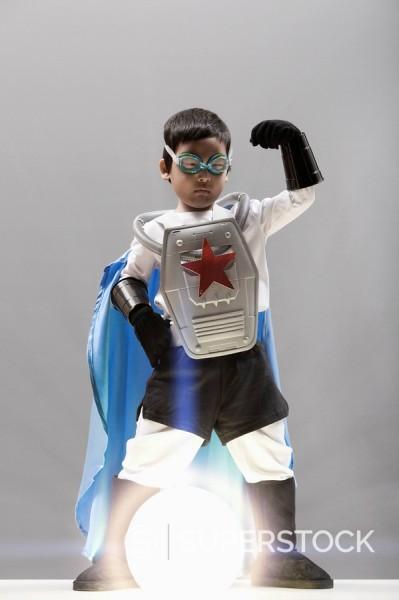 Korean boy in superhero costume standing over glowing orb : Stock Photo