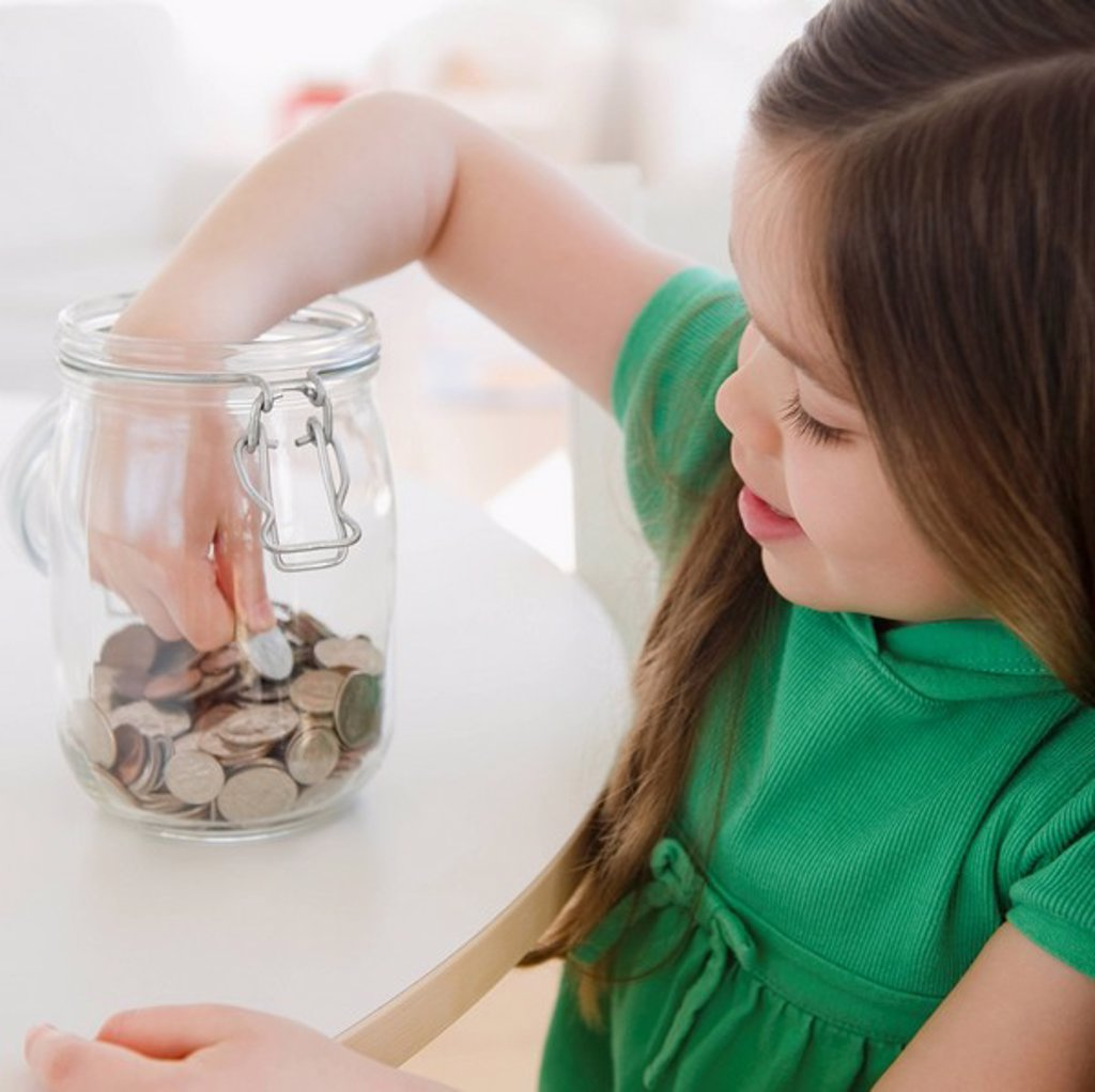 Mixed race girl taking coin out of jar : Stock Photo