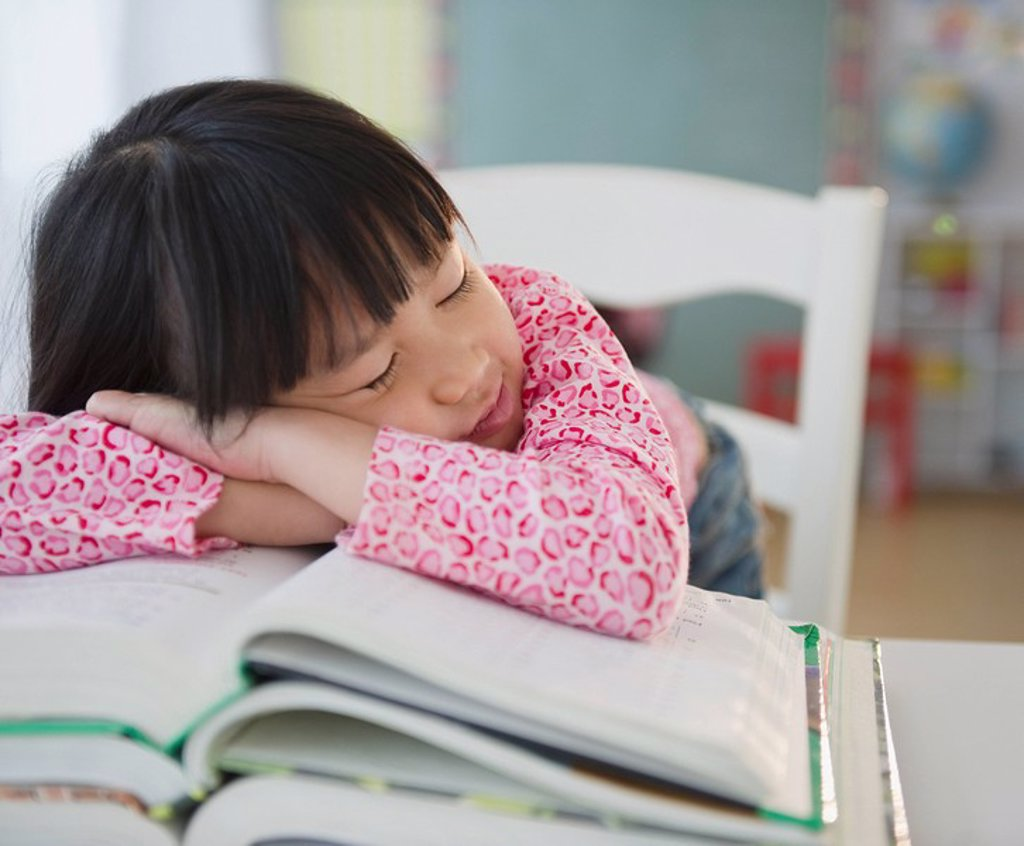 Stock Photo: 1589R-132025 Chinese girl napping on textbooks