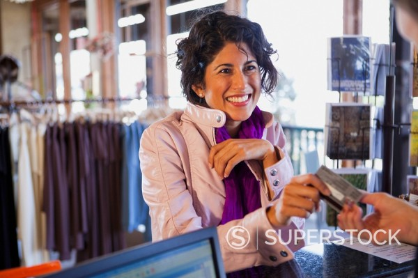Stock Photo: 1589R-132092 Ecuadorian woman handing credit card to clerk in clothing shop