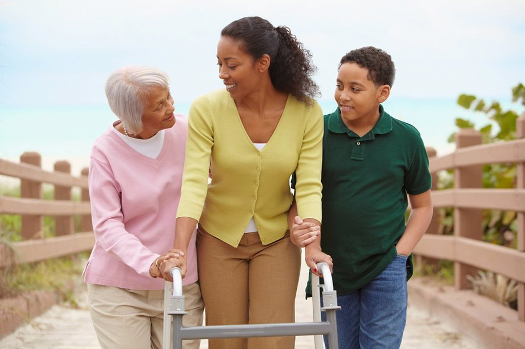 African American woman using walker with help of family : Stock Photo