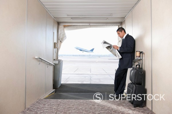 Stock Photo: 1589R-132258 Hispanic businessman standing on jetway