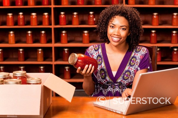 African American woman with laptop holding jar of sauce : Stock Photo