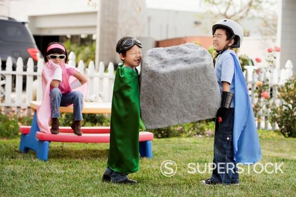 Korean children as superheros carrying large boulder : Stock Photo