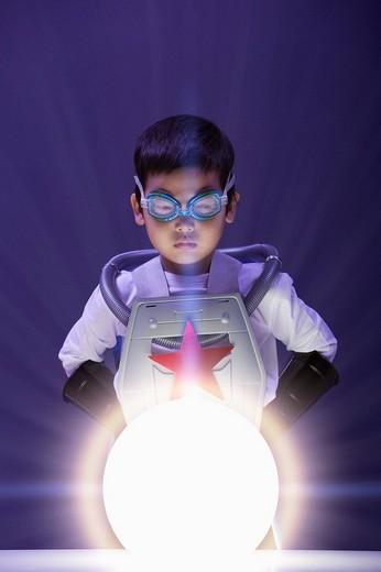 Korean boy in superhero costume looking at glowing orb : Stock Photo