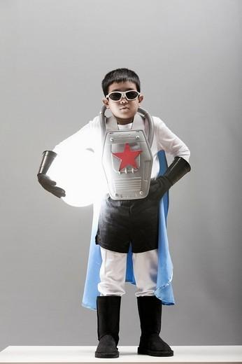 Korean boy in superhero costume holding glowing orb : Stock Photo