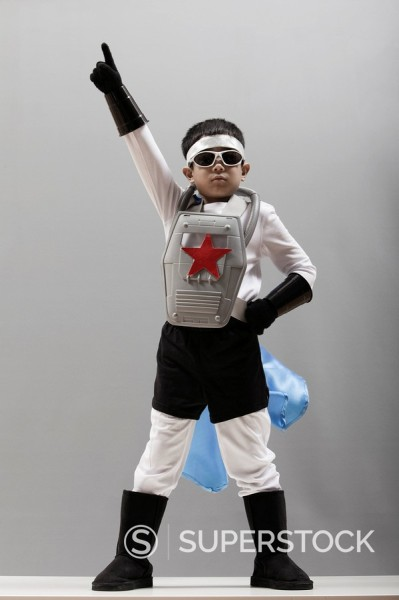 Korean boy in superhero costume with arm raised : Stock Photo