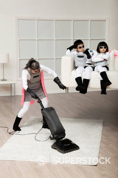 Stock Photo: 1589R-132310 Asian superhero mother lifting sofa to vacuum underneath