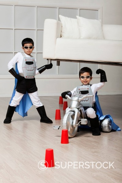 Stock Photo: 1589R-132312 Korean superhero boy lifting sofa for brother to ride underneath