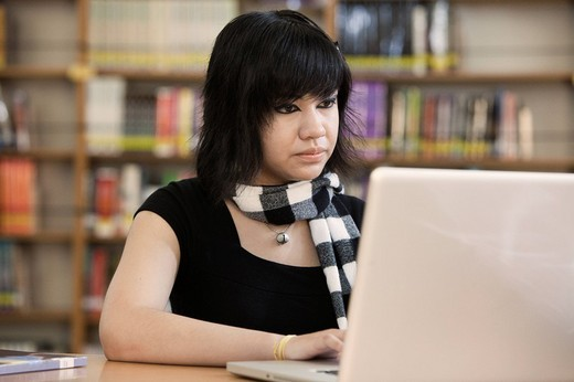 Hispanic student typing on laptop in school library : Stock Photo