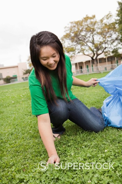 Asian student picking litter on school grounds : Stock Photo
