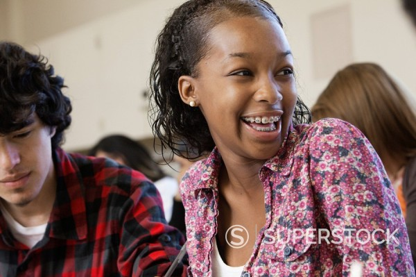 African American student laughing in classroom : Stock Photo