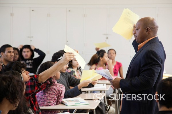 Teacher holding papers in classroom : Stock Photo