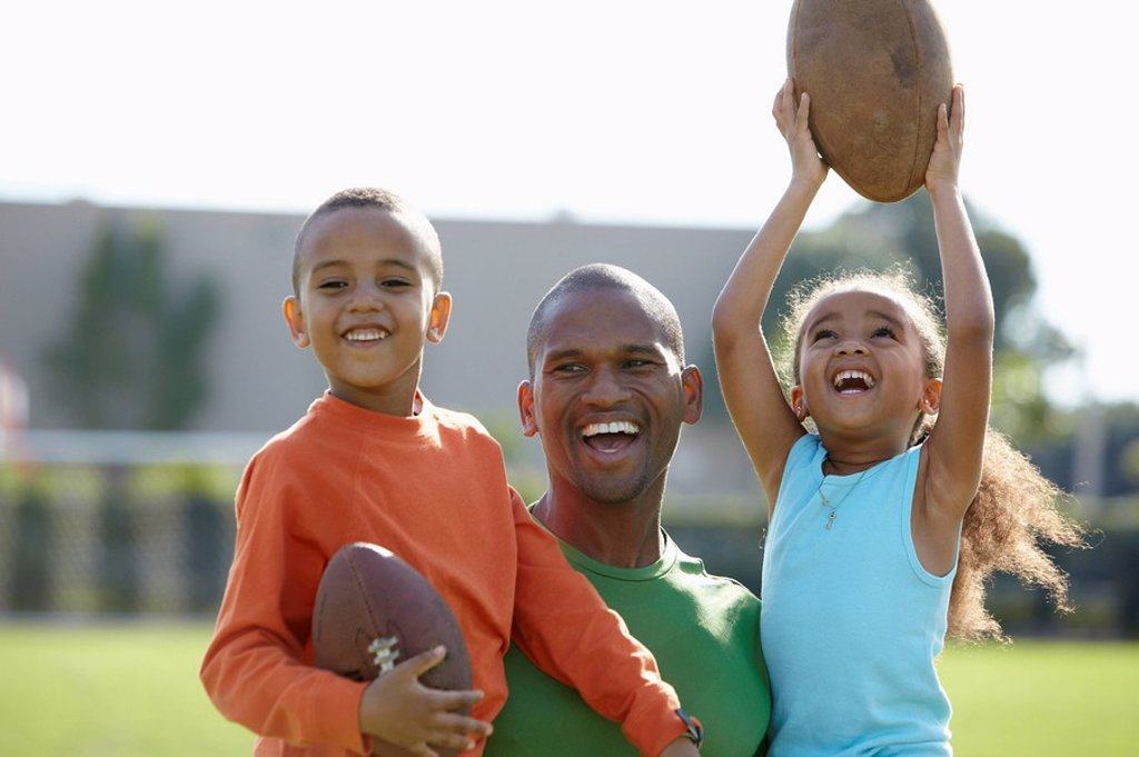 African American father, son and daughter playing football : Stock Photo