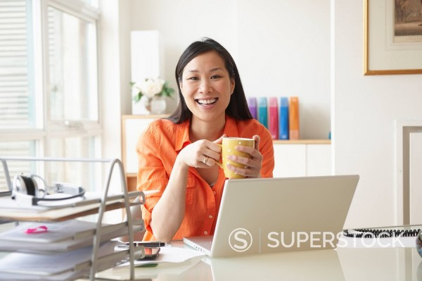 Chinese businesswoman drinking coffee at desk : Stock Photo