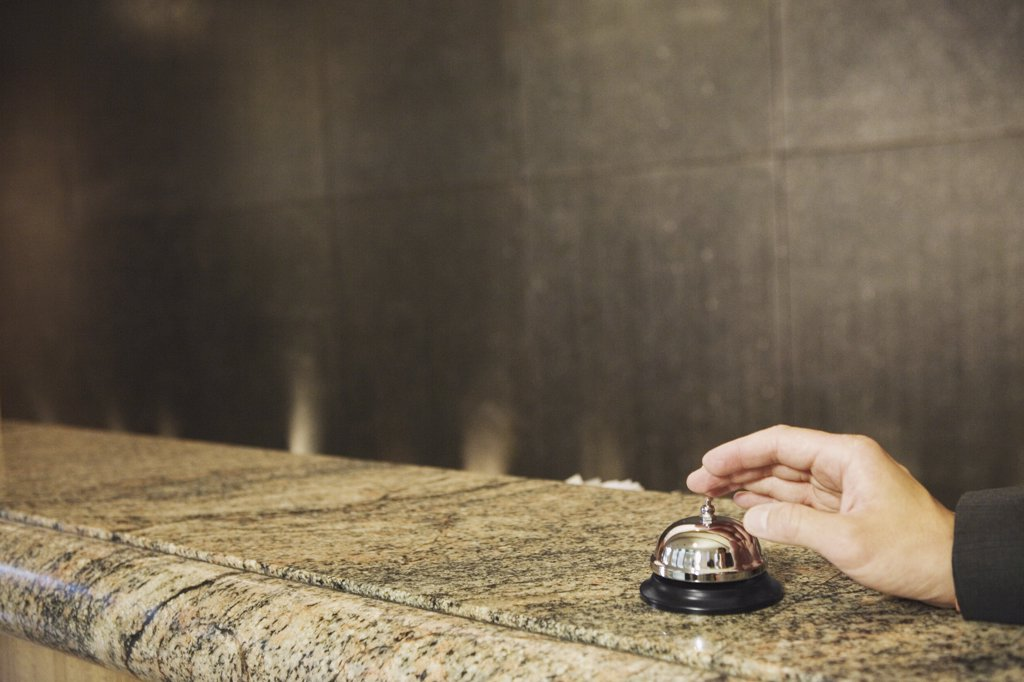 Hand reaching for service bell on counter : Stock Photo