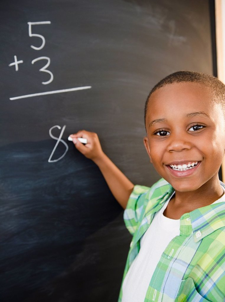 Stock Photo: 1589R-133062 Black boy solving math problems on blackboard