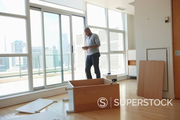 Stock Photo: 1589R-133126 African American man assembling cabinet