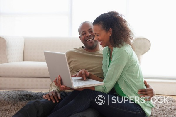 Couple in livingroom using laptop together : Stock Photo