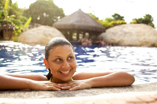 Smiling mixed race woman in swimming pool : Stock Photo