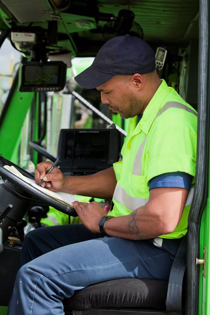 Stock Photo: 1589R-133915 African American man in garbage truck writing on clipboard