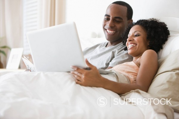 Stock Photo: 1589R-134011 Couple laying in bed using laptop